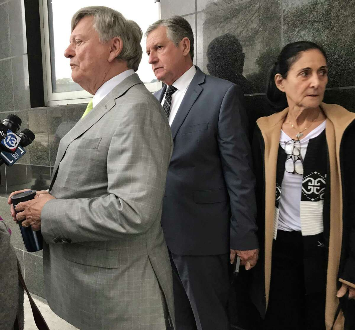Carlos and Jemima Guimaraes against wall with attorney Rusty Hardin outside the Bob Casey Federal courthouse in Houston after they were sentenced to federal prison on Wednesday, Dec 12, 2018, for aiding in the international kidnapping of their grandson Nicholas Brann.