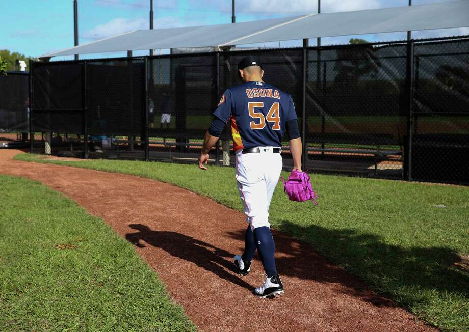Houston Astros right handed pitcher Roberto Osuna makes his way to the field with a pink glove at Fitteam Ballpark of The Palm Beaches on Day 1 of spring training on Thursday, Feb. 14, 2019, in West Palm Beach. A young fan told him that he likes Osuna's pink glove. Photo: Yi-Chin Lee, Houston Chronicle / © 2019 Houston Chronicle