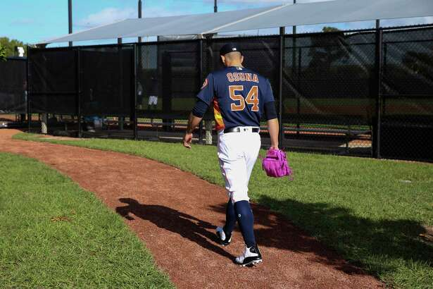 Houston Astros right handed pitcher Roberto Osuna makes his way to the field with a pink glove at Fitteam Ballpark of The Palm Beaches on Day 1 of spring training on Thursday, Feb. 14, 2019, in West Palm Beach. A young fan told him that he likes Osuna's pink glove.