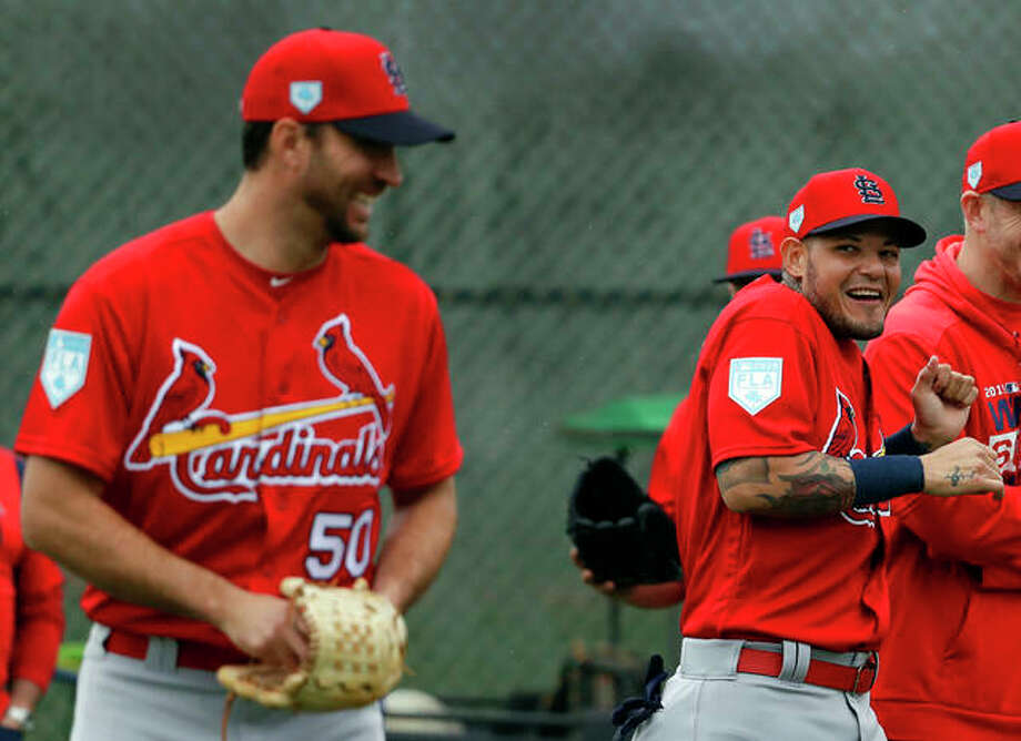 St. Louis Cardinals catcher Yadier Molina, right, laughs after receiving a kiss on the cheek from teammate Adam Wainwright, left, as Wainwright walked past during spring training baseball practice Wednesday, Feb. 13, 2019, in Jupiter, Fla. Photo: AP Photo | Jeff Roberson