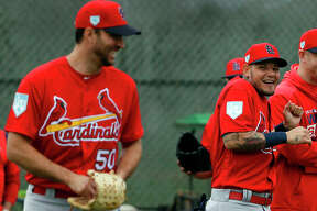 St. Louis Cardinals catcher Yadier Molina, right, laughs after receiving a kiss on the cheek from teammate Adam Wainwright, left, as Wainwright walked past during spring training baseball practice Wednesday, Feb. 13, 2019, in Jupiter, Fla.