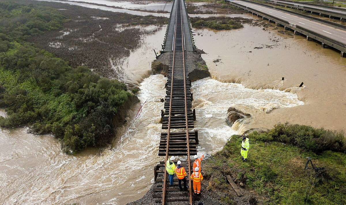 Caltrans workers examine railroad tracks suspended above flood waters following a levee break along highway 37 near Novato, Calif., on Thursday, Feb. 14, 2019. Water from Novato Creek was sent rushing beneath the tracks after the ground below gave way.
