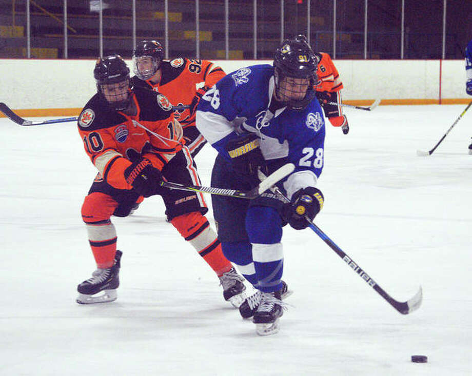 Edwardsville senior Mitchell Oberlag, left, tries to defend the Ladue puck handler during a Challenge Cup game at the East Alton Ice Arena. Photo: Scott Marion/Intelligencer