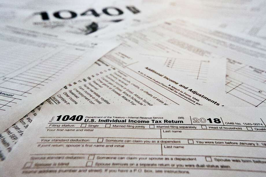 This Wednesday, Feb. 13, 2019, in Zelienople, Pa., shows multiple forms printed from the Internal Revenue Service web page that are used for 2018 U.S. federal tax returns. The government says that the average tax refund and the total amount of refunds issued have declined for the second straight week. The declines have become a political issue, as Democrats contend they show how the new Republican-written tax law hurts middle-class people. (AP Photo/Keith Srakocic) Photo: Keith Srakocic, Associated Press