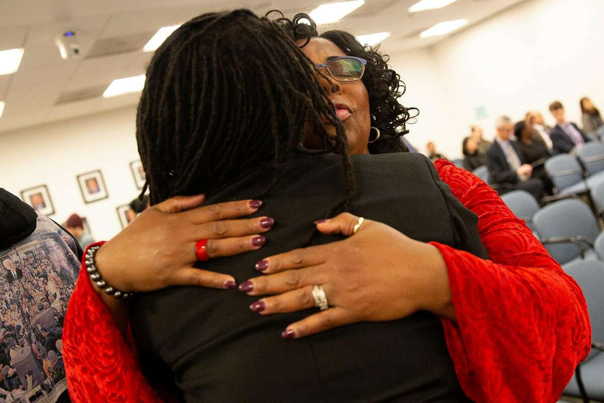 Wanda Johnson (right), mother of the late Oscar Grant, is embraced by BART's District 7 board director Lateefah Simon after a vote to name a street Oscar Grant Way on Thursday, Feb. 14, 2019, in Oakland, Calif.