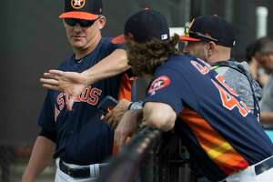 Houston Astros manager AJ Hinch talks to pitcher Gerrit Cole and bullpen catcher Javier Bracamonte at Fitteam Ballpark of The Palm Beaches on Day 1 of spring training on Thursday, Feb. 14, 2019, in West Palm Beach.