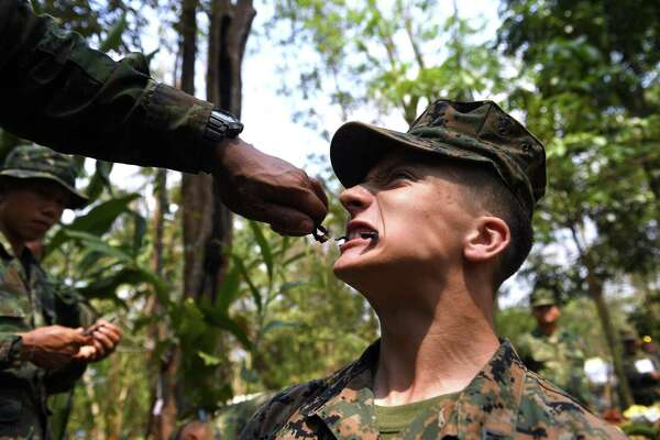 A US Marine soldier eats a scorpion during a jungle survival training with Thai soldiers in the joint 'Cobra Gold' military exercise in Chantaburi province on February 14, 2019. - The US and Thailand hold on February 14, the annual joint 'Cobra Gold', the largest US-led military exercises in Asia involving gruelling drills in the Thai jungle, war games, humanitarian assistance and disaster relief exercise. (Photo by Lillian SUWANRUMPHA / AFP)LILLIAN SUWANRUMPHA/AFP/Getty Images