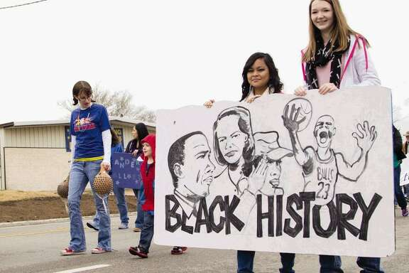 Two girls hold a sign made by Anderson Elementary minutes before The J-Mac 56th Annual Black History Parade in downtown Conroe, Aug. 5, 2017. A reader believes it is important to honor those who fought for social and racial equality by putting their words into practice.