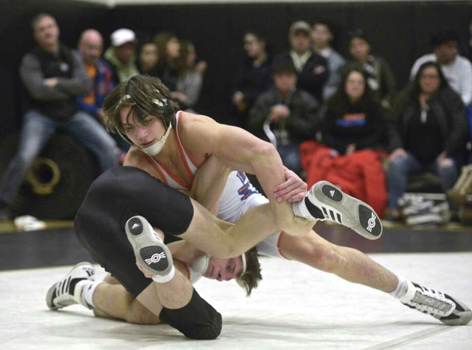 Trumbull's Jon Kosak, in black, and Danbury's Ryan Jack, in white, wrestle in the 126-pound weight class during a Jan. 16 match. Photo: H John Voorhees III / Hearst Connecticut Media / The News-Times
