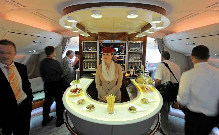 FILE- In this July 13, 2010, file photo Nadine Schumacher, center, works at the bar in the first class section on board Airbus A380 passenger plane of Emirates Airline during the International Air Show ILA at Schoenefeld airport in Berlin. European plane maker Airbus said Thursday, Feb. 14, 2019, that it will stop making its superjumbo A380 in 2021 for lack of customers, abandoning the world's biggest passenger jet and one of the aviation industry's most ambitious and most troubled endeavors. (AP Photo/Jens Meyer, File) Photo: Jens Meyer / AP2010