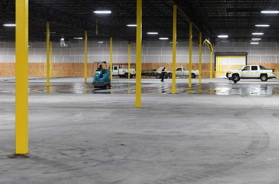 A worker drives a machine that cleans the floor at the former Groves' Kmart that is being converted into a climate controlled storage facility.