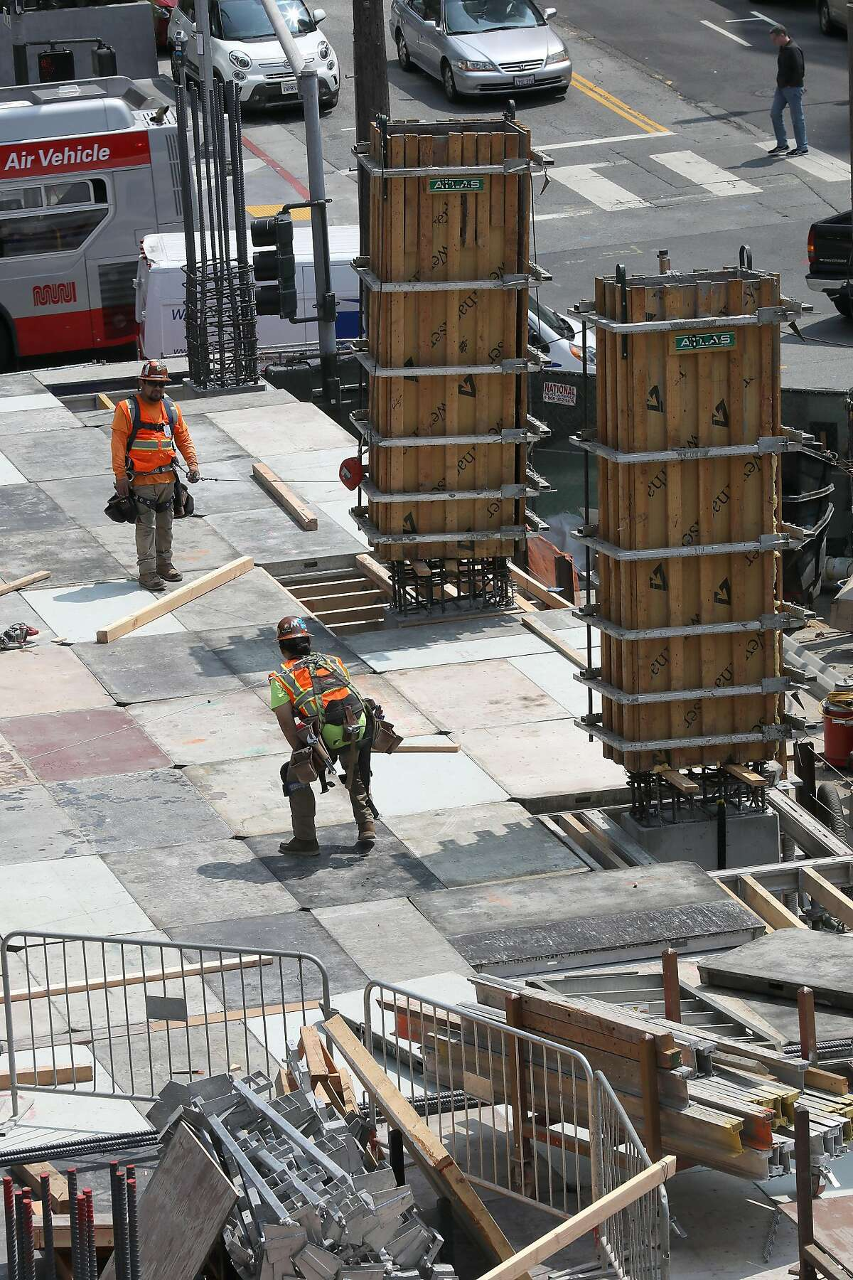 Construction workers next to columns at 160 Folsom St., a former parking lot near the Temporary Transbay Transit Center, where a condo tower is under construction on Friday, Aug. 24, 2018 in San Francisco, Calif.