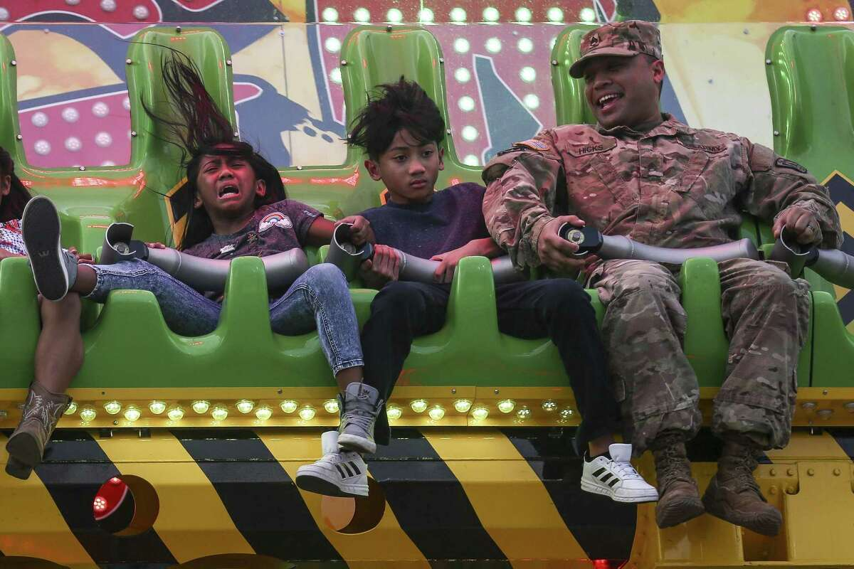 Army Staff Sgt. Christopher Hicks, right, laughs as he watch his daughter, Audrena Hicks, left, and son, Ezekiel Hicks, center, react on a ride at the Houston Livestock Show and Rodeo.
