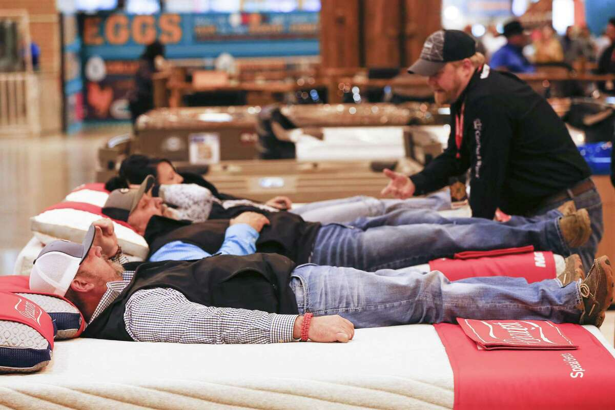 Attendees of the The Houston Livestock Show and Rodeo try out mattress in the NRG Center Friday, March 2, 2018, in Houston. ( Steve Gonzales / Houston Chronicle )