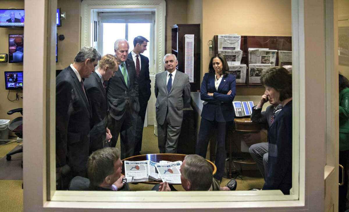 Senate Intelligence Committee Vice Chairman Mark Warner, D-Va., seated left with Chairman Richard Burr, R-N.C.,seated right, confer with committee members prior to a news conference on improving the nation's election infrastructure ahead of the 2018 midterm elections, on Capitol Hill in Washington, Tuesday, March 20, 2018. Standing from left are Intelligence Committee members Sen. Joe Manchin, D-W.Va., Sen. James Lankford, R-Okla., Sen. John Cornyn, R-Texas, Sen. Tom Cotton, R-Ark., Sen. Jack Reed, D-R.I., Sen. Kamala Harris, D-Calif., and Sen. Susan Collins, R-Maine. (AP Photo/J. Scott Applewhite)