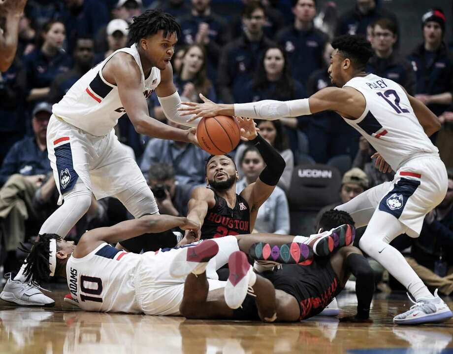 Connecticut's Josh Carlton, left, Houston's Galen Robinson Jr., center, and Connecticut's Tyler Polley, right, reach for the ball as Connecticut's Brendan Adams, bottom left, and Houston's Corey Davis Jr., bottom, right, are tangled together during the first half of an NCAA college basketball game, Thursday, Feb. 14, 2019, in Hartford, Conn. (AP Photo/Jessica Hill) Photo: Jessica Hill / Associated Press / Copyright 2019 The Associated Press. All rights reserved