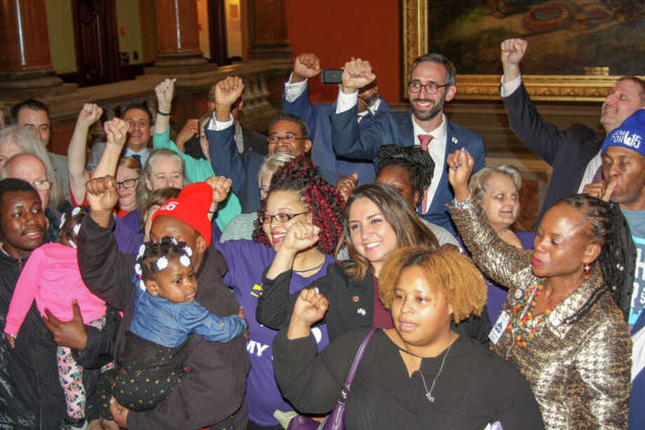 State Rep. Will Guzzardi joins activists on the Capitol rotunda after the bill to raise the state's minimum wage to $15 by 2025 passed the Illinois House on Thursday afternoon. The legislation, sponsored by Guzzardi, a Chicago Democrat, passed along partisan lines 69-47-1. Photo: Jerry Nowicki | Capitol News Illinois