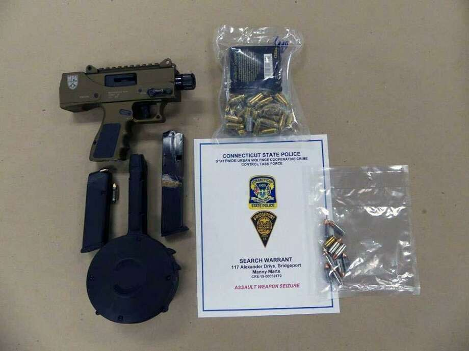 A search in Bridgeport, Conn., led police to a stolen gun, a 50-round drum, a .30-round extended magazine and 67 rounds of ammunition on Feb. 14, 2019. Photo: Contributed Photo / Connecticut State Police / Contributed Photo / Connecticut Post Contributed
