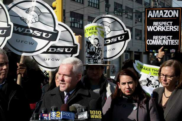 New York City Councilman Jimmy Van Bramer, second from left, speaks during a press conference in Gordon Triangle Park in the Queens borough of New York, following Amazon's announcement it would abandon its proposed headquarters for the area, Thursday Feb. 14, 2019. (AP Photo/Bebeto Matthews)