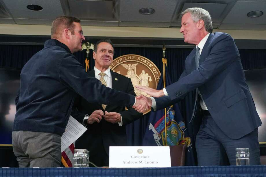 From left: John Schoettler, Amazon's vice president for global real estate and facilities; Gov. Andrew Cuomo; and Mayor Bill de Blasio at a news conference in New York, Nov. 13, 2018. Amazon's sudden decision on Feb. 14, 2019, to cancel its plan to build a corporate campus in Long Island City, Queens, amounted to a stunning rejection for the two often-at-odds politicians who had heralded its arrival, Cuomo and de Blasio, and the biggest win yet for emboldened left-wing progressives in New York. (Chang W. Lee/The New York Times) Photo: CHANG W. LEE / NYTNS