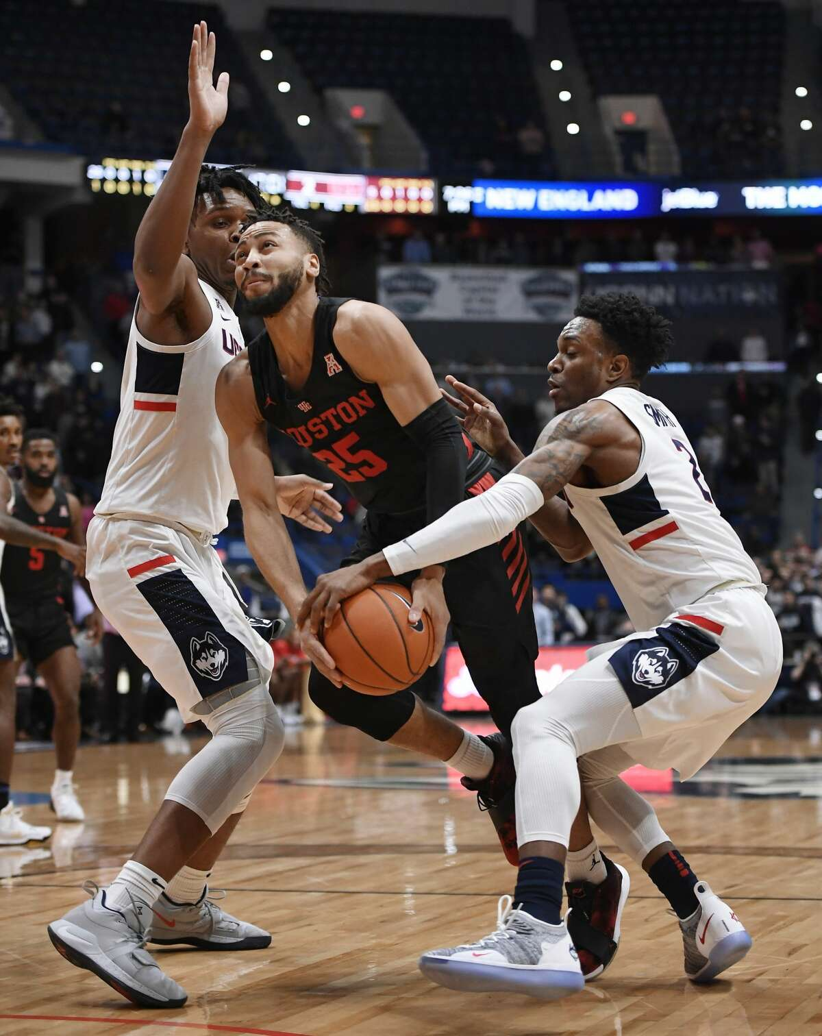 Connecticut's Tarin Smith, right, strips the ball from Houston's Galen Robinson Jr. (25) as Connecticut's Josh Carlton, left, defends during the first half of an NCAA college basketball game, Thursday, Feb. 14, 2019, in Hartford, Conn. (AP Photo/Jessica Hill)