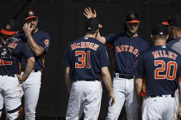 Houston Astros starting pitchers Justin Verlander, from left, Collin McHugh, Gerrit Cole and Wade Miley (20) talk to catcher Max Stassi and bullpen coach Josh Miller after pitching at Fitteam Ballpark of The Palm Beaches on Day 1 of spring training on Thursday, Feb. 14, 2019, in West Palm Beach.