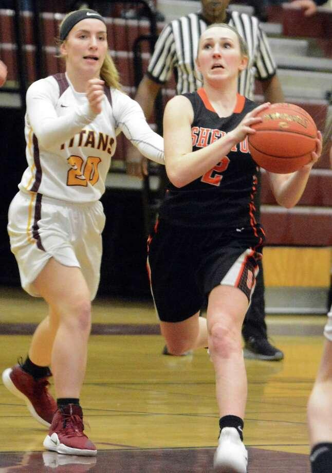 Shelton's Maggie Howard dribbles to basket as Sheehan's Jayne Mackenzie defends on Thursday. Photo: Dave Phillips / For Hearst Connecticut Media