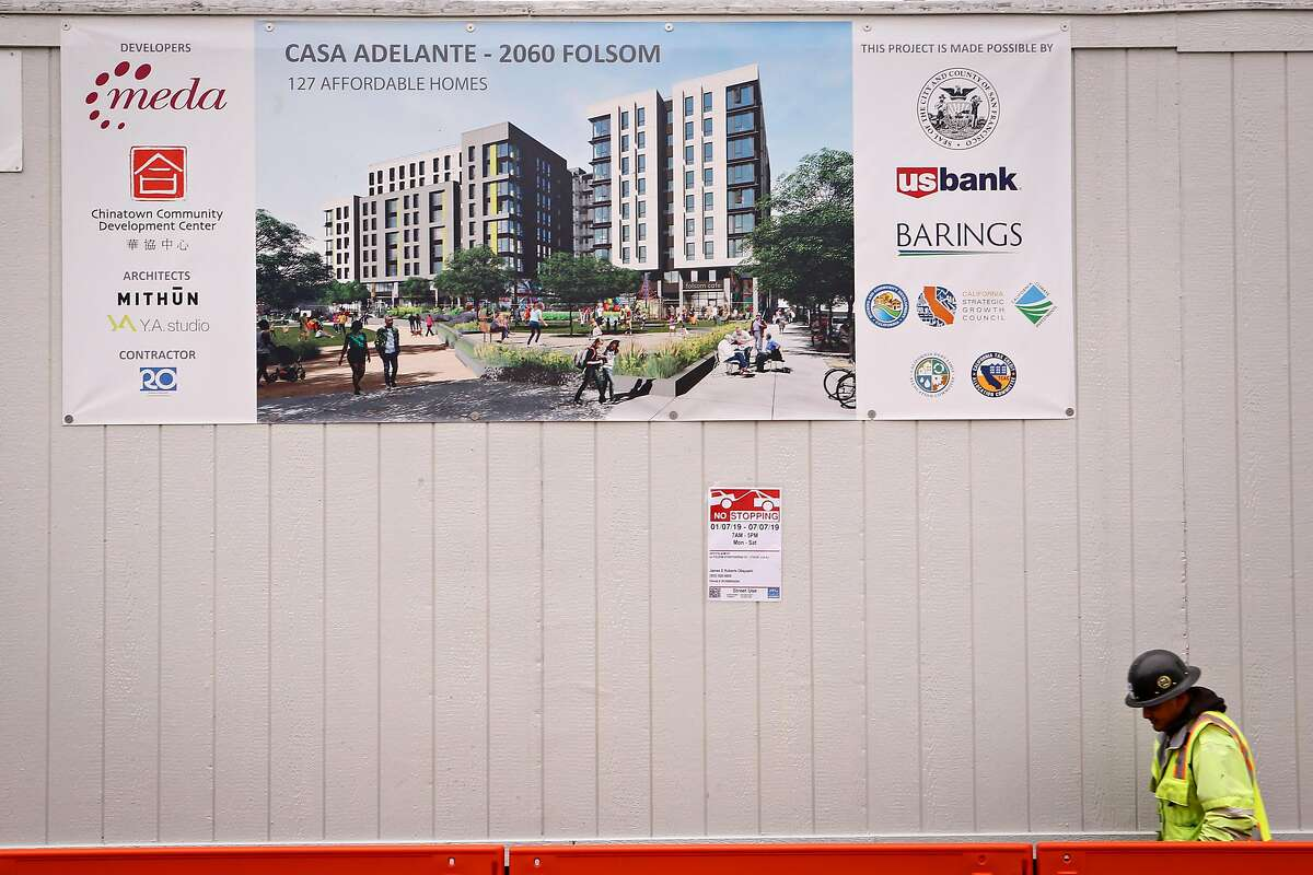 A construction worker walks past a large rendering of the new affordable housing building construction site at 2060 Folsom St. on Tuesday on Tuesday, February 12, 2019 in San Francisco, Calif.