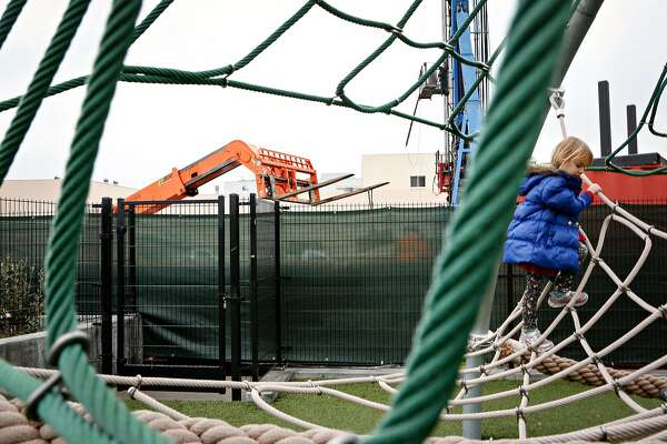 A forklift from a new affordable housing construction site is seen as Josephine Milbrath, 4, plays on the playground at Chan Kaajal Park on Tuesday, February 12, 2019 in San Francisco, Calif. The affordable housing site will be integrated with Chan Kaajal Park.