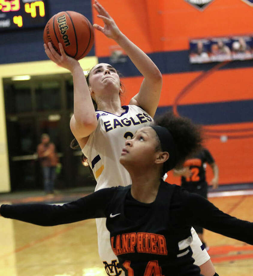 CM's Anna Hall (back) puts up a shot in the lane over Springfield Lanphier's Cheyenne Trotter in the fourth quarter Thursday night in the championship game of the Rochester Class 3A Regional. Hall finished with 33 points and 15 rebounds in the Eagles' win. Photo: Greg Shashack / The Telegraph