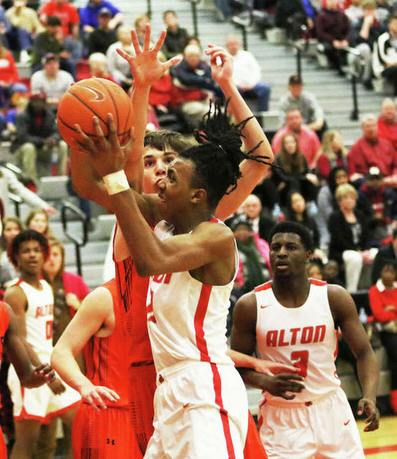 Alton's Donovan Clay shoots over an Edwardsville defender during a Redbirds' SWC victory last month at Alton High in Godfrey. The teams met again Thursday in Edwardsville with the Redbirds winning again at Lucco-Jackson Gym. Photo: Greg Shashack / The Telegraph