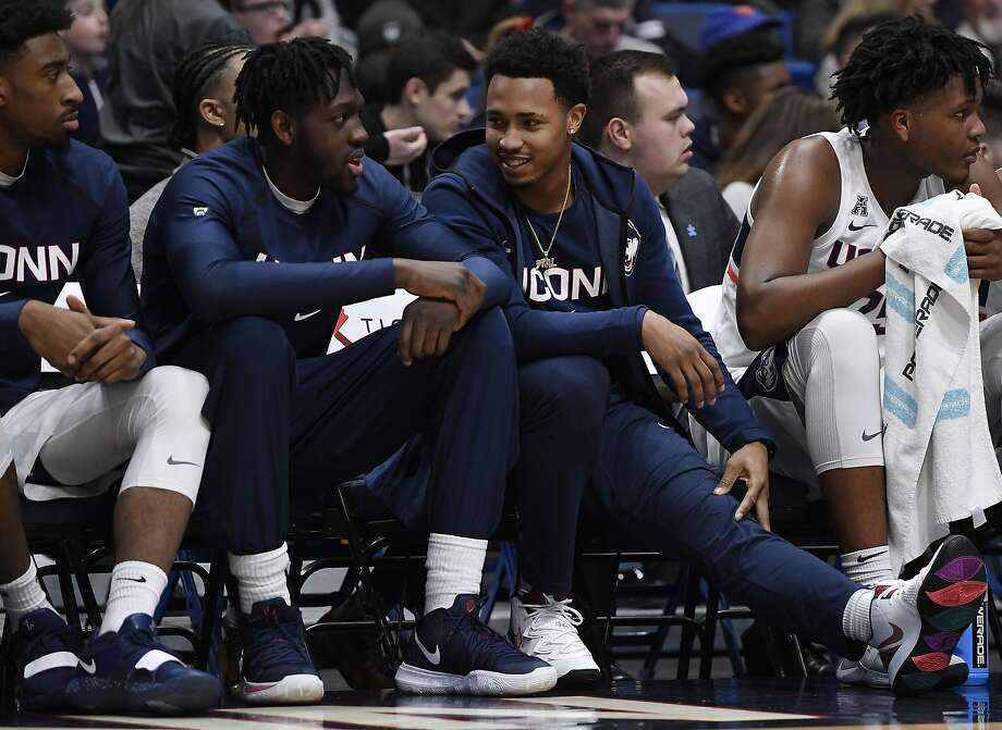 Connecticut starter Jalen Adams, who is out injured, right, talks with teammate Mamadou Diarra, left, during the first half of an NCAA college basketball game against Houston, Thursday, Feb. 14, 2019, in Hartford, Conn. (AP Photo/Jessica Hill) Photo: Jessica Hill, Associated Press