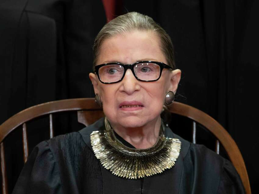 FILE - In this Nov. 30, 2018 file photo, Associate Justice Ruth Bader Ginsburg sits with fellow Supreme Court justices for a group portrait at the Supreme Court Building in Washington. Ginsburg has missed a month of Supreme Court arguments as she recovers from lung cancer surgery. But she?s not the first justice to be away for a while and her absence hardly compares with those of some of her predecessors. (AP Photo/J. Scott Applewhite)