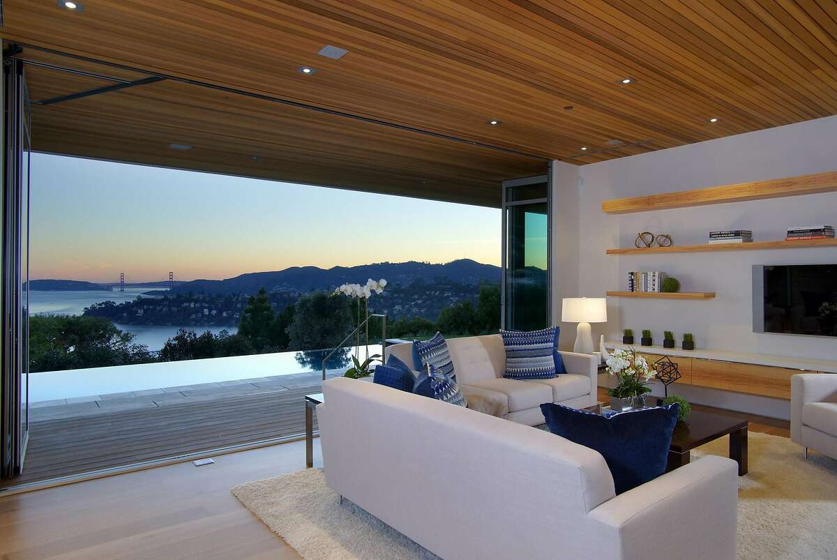This lower level family room at 1860 Mountain View Drive in Tiburon, with collapsible glass walls opening to a deck, and infinity edge pool and unobstructed views of the Golden Gate Bridge, was designed by Marin-based Amalfi West.