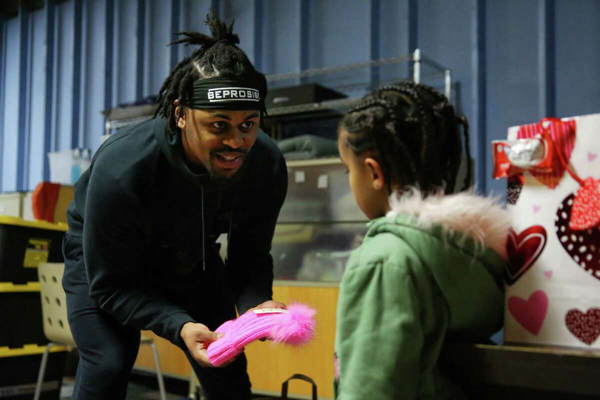 Seahawks running back C.J. Prosise hands out gifts to kids on Valentine's Day at the Mary's Place Emergency Shelter in downtown Seattle, Feb. 14, 2019.