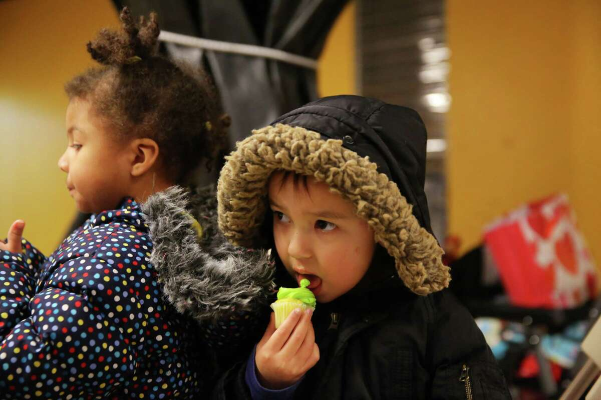 Kids eat Seahawks themed cupcakes after Seahawks running back C.J. Prosise handed out gifts to on Valentine's Day at the Mary's Place Emergency Shelter in downtown Seattle, Feb. 14, 2019.