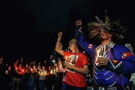 Scott Rehaune, right, holds up his fist with other attendees during the 3rd annual Missing and Murdered Indigenous Woman's candlelight memorial vigil hosted by UW First Nations, Thursday, at w???b?altx? Intellectual House on University of Washington campus, Feb. 14, 2019. Over 100 attendees wore red, prayed and sang together, spoke about their loved ones who are missing or have been murdered and joined together to light candles and hold space for their absent loved ones.