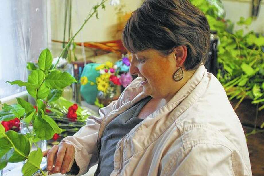 Karen Anderson prepares a floral design Wednesday at Barber Florist. Anderson owns a photography business but helps at the florist shop during busy holidays. Photo: Rosalind Essig | Journal-Courier