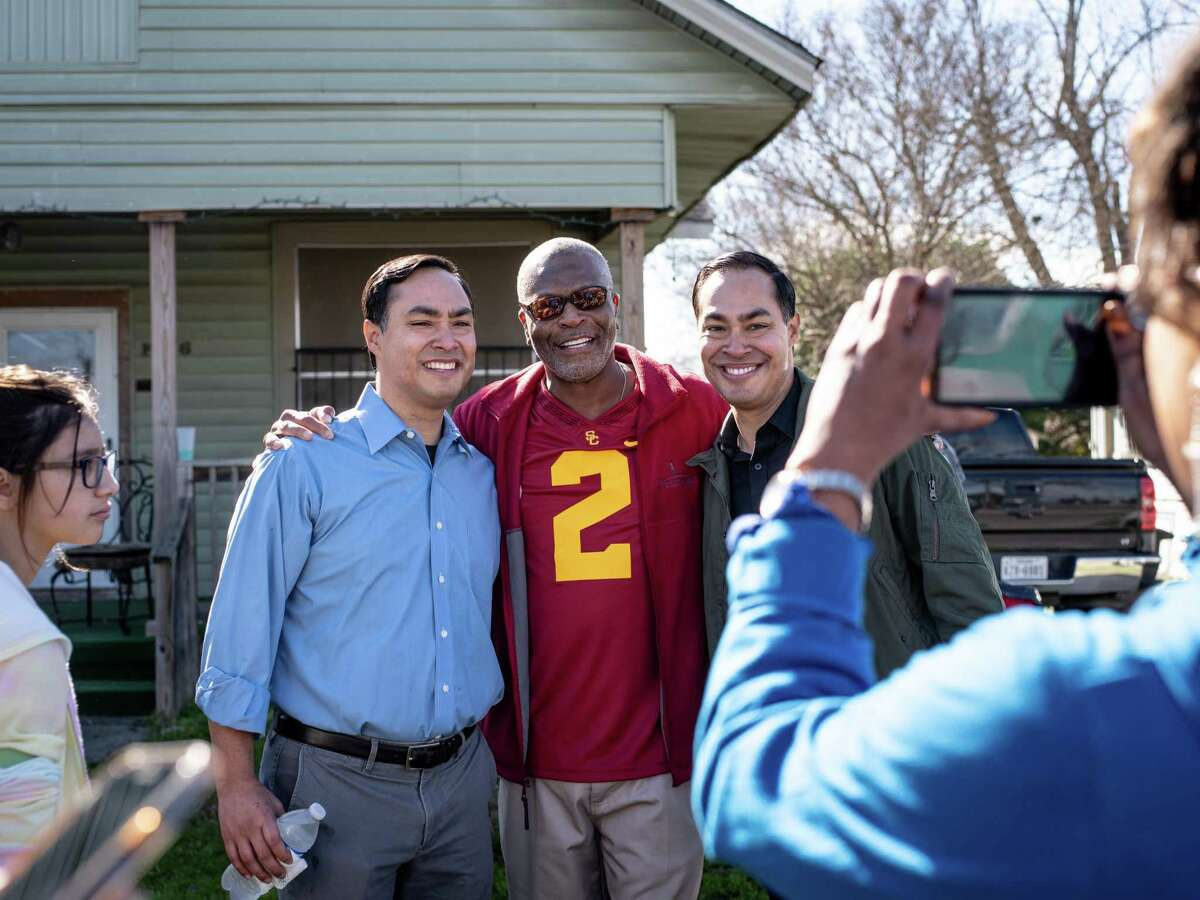 Former United States Secretary of Housing and Urban Development and Democratic candidate for president 2020 Julian Castro, right, and his brother United States House of Representative for Texas's 20th congressional district Joaquin Castro, left, take photos with a supporter during the Martin Luther King Jr. day march in San Antonio, Texas on Monday, January 21, 2019.