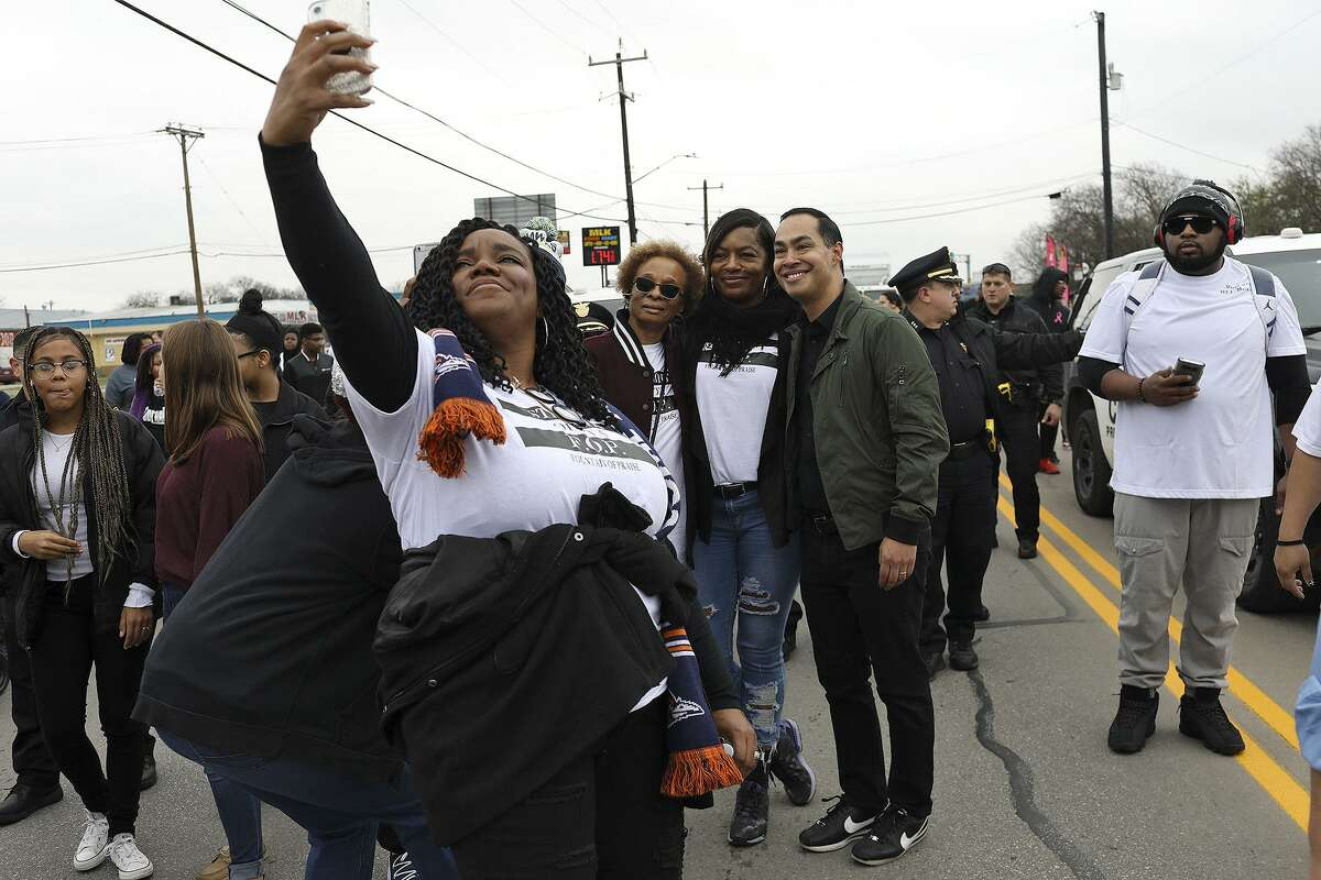 Presidential candidate Julián Castro greets supporters and poses for photos as he walks in the Martin Luther King Jr. March in San Antonio on Monday, Jan. 21, 2019.