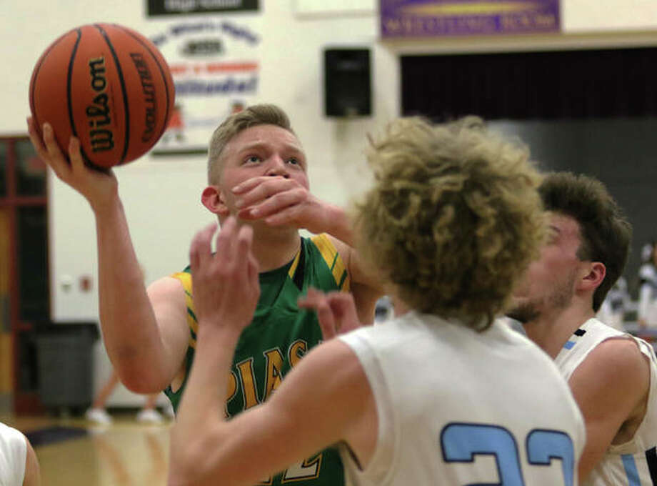 Southwestern's Brady Salzman (left), shown shooting in traffic against North Mac in the Macoupin County Tourney at Mount Olive, and the Piasa Birds closed their regular season Thursday night with a SCC victory over Carlinville. Photo: Greg Shashack / The Telegraph