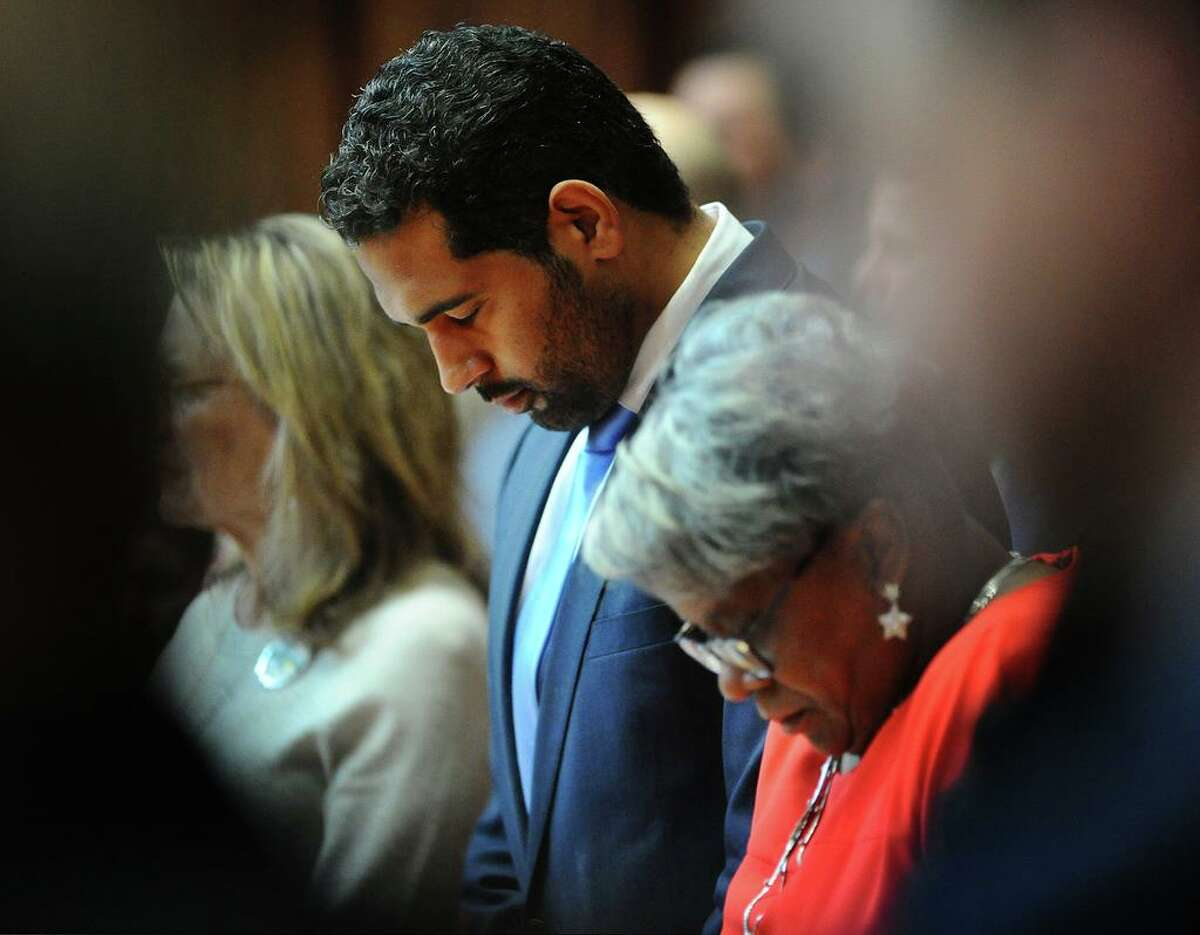 State senators Dennis Bradley, D-Bridgeport, and Marilyn Moore, D-Bridgeport, bow their heads in prayer during the opening session of the senate at the Capitol in Hartford, Conn. on Wednesday, January 9, 2019.