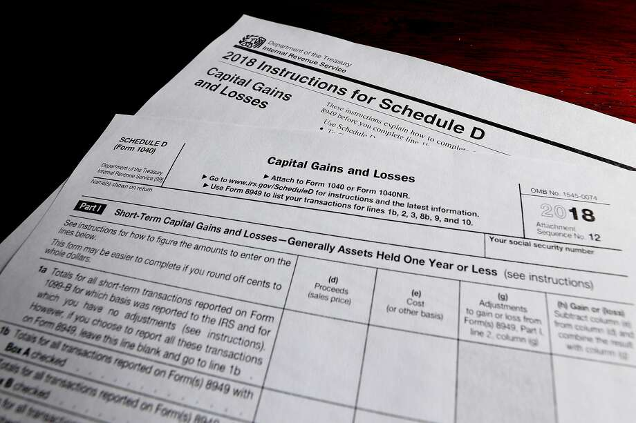 """This Wednesday, Feb. 13, 2019, in Zelienople, Pa., shows schedule D for form 1040 and instructions printed from the Internal Revenue Service web page that are used for 2018 U.S. federal tax returns. As if the worst year for stocks in nearly a decade weren't bad enough, many investors now have to pay a tax bill on top of it. The headache for investors is a result of how mutual funds are structured and how many times the funds' managers bought and sold shares through 2018. Because of the way tax laws work, the majority of investors with a U.S. stock mutual fund or ETF received something called a """"capital-gains distribution"""" late last year. (AP Photo/Keith Srakocic, File) Photo: Keith Srakocic / Associated Press"""