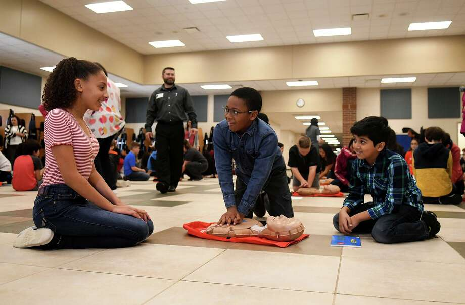 Jace Watson, 10, center, with fellow Bernshausen Elem. 5th graders Kailee Chulu, 10, left, and Ammar Shariq, 10, right, practices his CPR technique during a basics of CPR class led by BES School Nurse Elizabeth Goedde, Klein Cain High School School Nurse Emily Berry, KCHS Health Science students, and Northwest Alliance EMS (Community Health) clinical educators in the BES cafeteria on Feb. 14, 2019. Photo: Jerry Baker, Houston Chronicle / Contributor / Houston Chronicle