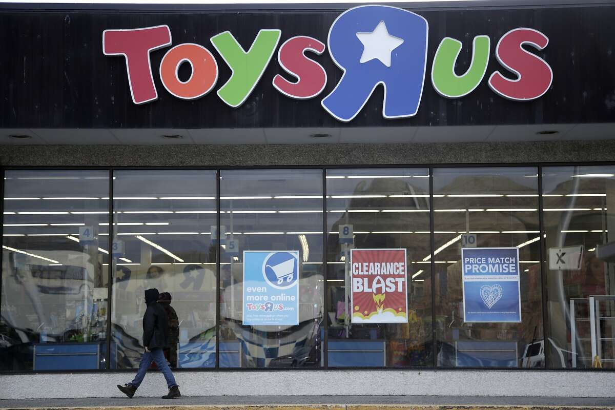 FILE - In this Jan. 24, 2018, file photo, a person walks near the entrance to a Toys R Us store, in Wayne, N.J.