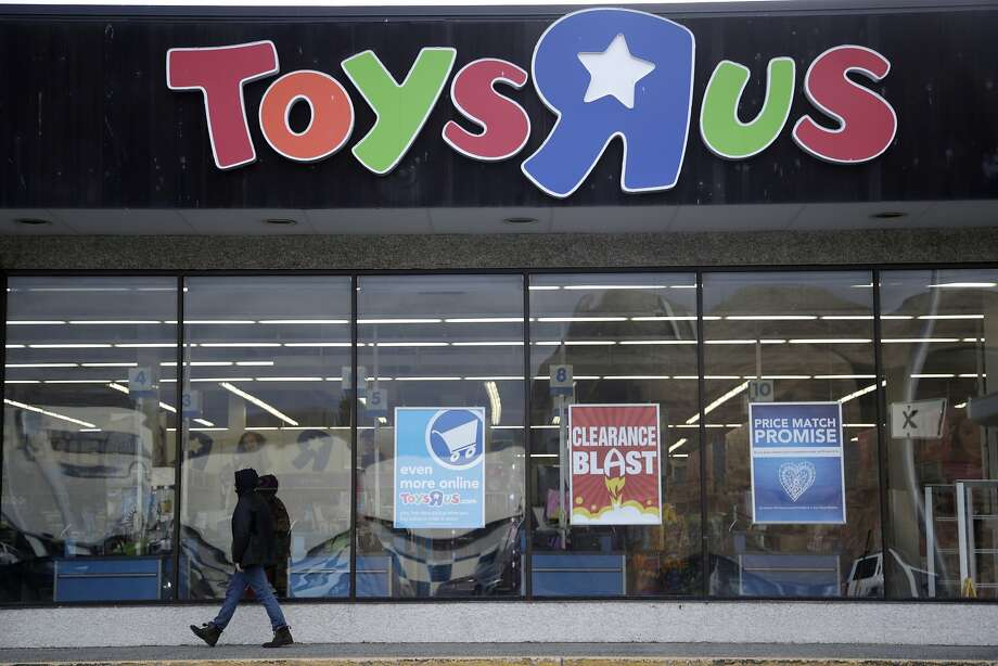FILE - In this Jan. 24, 2018, file photo, a person walks near the entrance to a Toys R Us store, in Wayne, N.J. A group of investors is planning a potential comeback for Geoffrey the giraffe and his crew. Investors that control the assets of the company say they now see a better chance of a return on investment by potentially reviving the toy chain, rather than selling it off for parts. (AP Photo/Julio Cortez, File) Photo: Julio Cortez, Associated Press