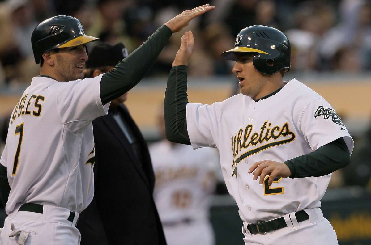 Oakland Athletics' Adam Rosales, left, and Cliff Pennington celebrate after both scored on a double by Rajai Davis against the San Francisco Giants during the third inning of a baseball game in Oakland, Calif., Friday, May 21, 2010. (AP Photo/Jeff Chiu)