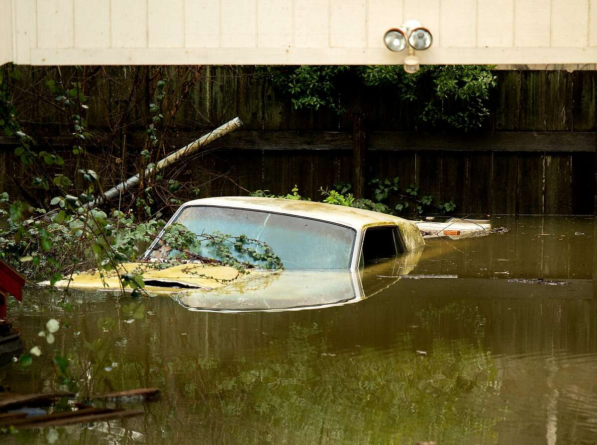 Floodwaters surround a parked car as the Russian River overflows its banks in Guerneville, Calif., on Friday, Feb. 15, 2019.
