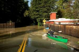Sean O'Connor canoes through floodwaters on Neeley Rd. on Friday, Feb. 15, 2019. The Russian River overflowed its banks flooding some streets before waters started to recede Friday morning.