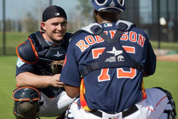 Houston Astros catcher Max Stassi (12) talks to fellow catcher Chuckie Robinson (75) during practice at Fitteam Ballpark of The Palm Beaches on Day 2 of spring training on Friday, Feb. 15, 2019, in West Palm Beach.